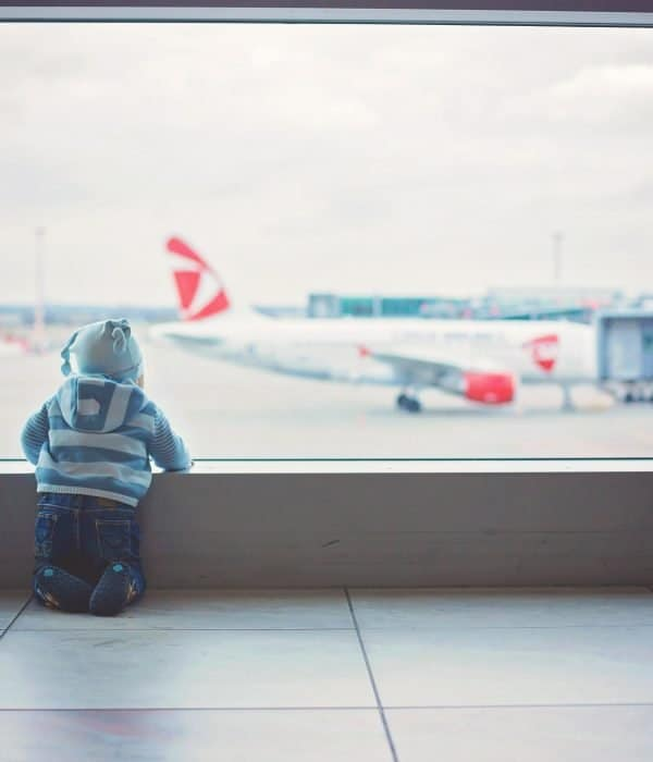 A child watching airplanes out the window. He is waiting for his plane to depart.