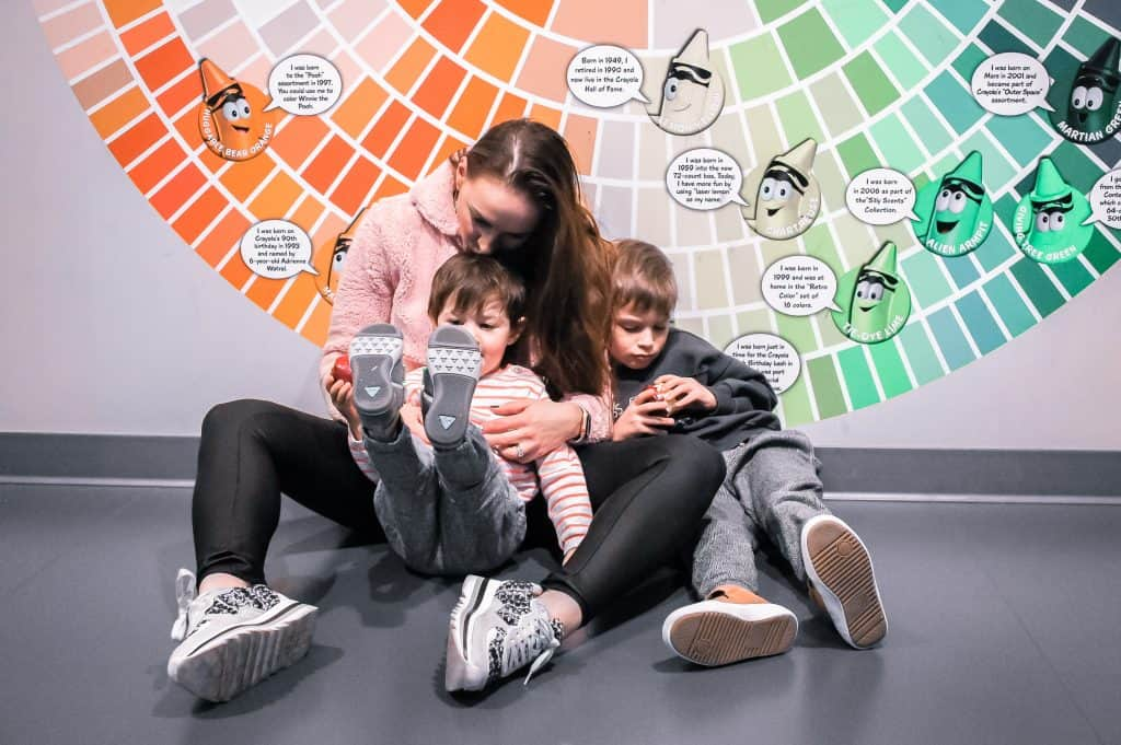 Crayola Experience Review at Mall of America - Me sitting on the floor with kids against the Crayola colors wall backdrop (Ilan has his feet up playing and I am kissing him on top of his head)