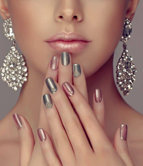 Press-on Nails | A crop of a face of a beautiful woman with cascading earrings and beautifully done nails.