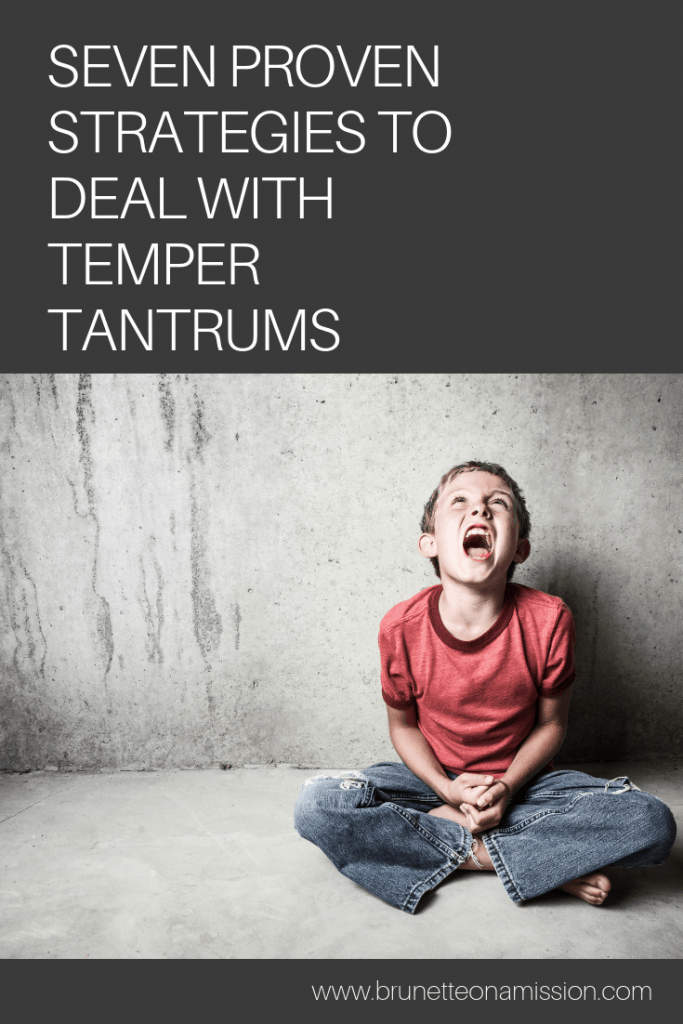 A child yelling sitting on the floor leaning against the wall in the middle of a temper tantrum.