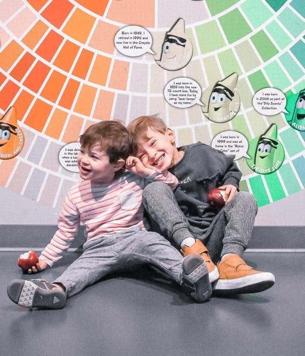 Two toddlers laughing sitting on the floor against a color wall at the Mall of America.