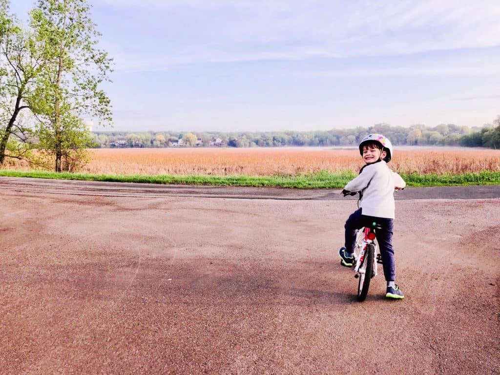 Toddler on his first pedal bike standing on a trail looking over a vast plain and a blue skyline