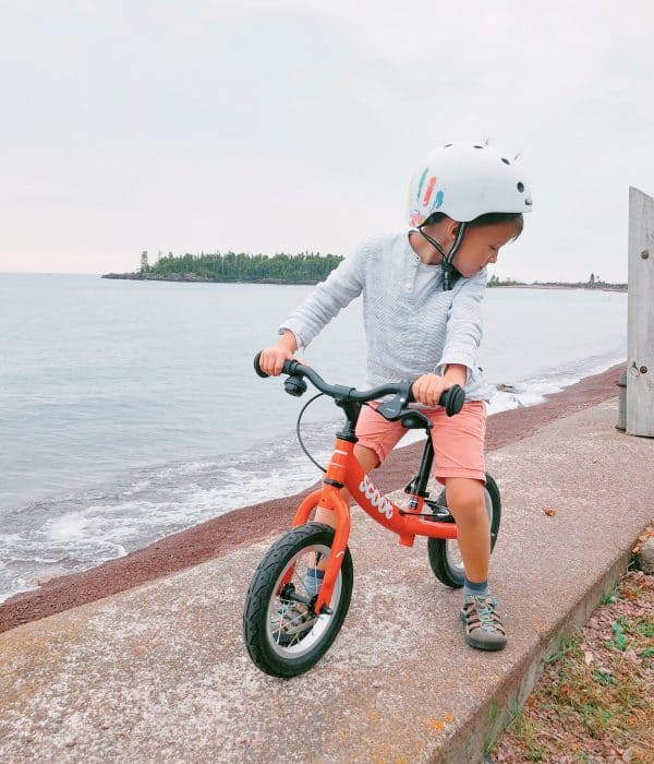 Toddler on a red balance bike from Ridgeback Scoot on the beach in Grand Marais | Brunette on a Mission Blog | #balancebikes
