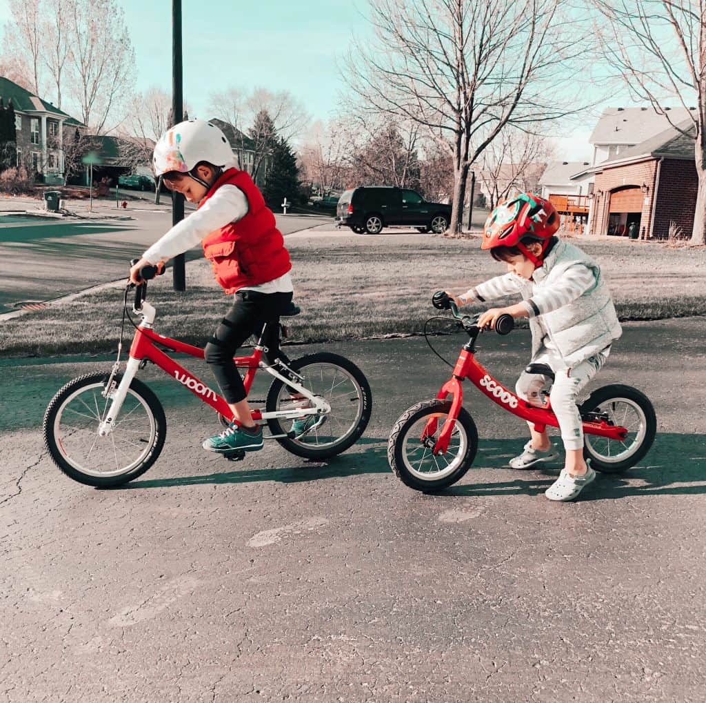 A preschooler on a pedal bike and a toddler on a balance bike getting ready to go on a bike ride.