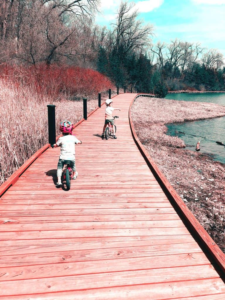 Young children riding their bikes in Spring on a boardwalk near a pond.