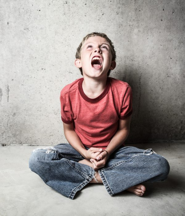 Angry and screaming child in the middle of a tantrum sitting on the floor leaning on a wall.