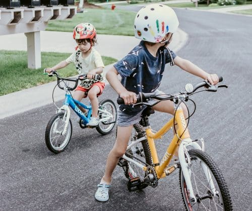 A 6-year-old and a 3-year-old riding their pedal bikes without training wheels or stabilizers on a neighborhood street.