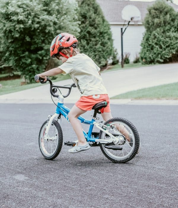 3-year-old toddler boy pushing off as he is starting to pedal a bike without training wheels on the road. #brunetteonamissionblog #toddlersbiking #learningtobike #balancebike #startingtobike