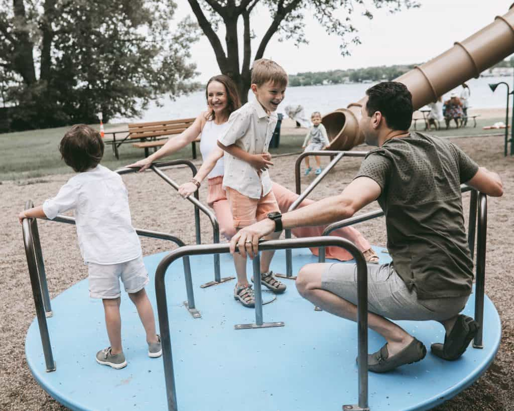 On a carousel at a playground with our two kids | Brunette on a Mission Blog | #uniquefamilyphotos