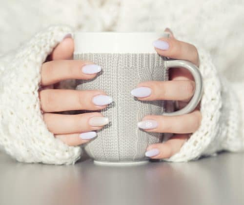 5 Best Press-on Nails to Try in 2020 - Faux Nail Reviews | Close up of woman's hands holding cup of hot coffee drink. She is wearing warm cardigan. Winter chill out and lifestyle concept.