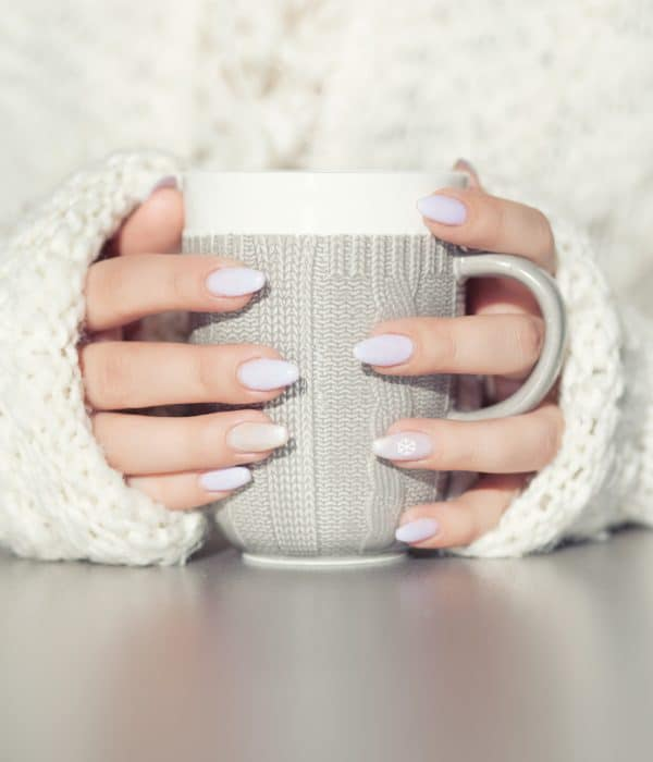 5 Best Press-on Nails to Try in 2019 - Faux Nail Reviews | Close up of woman's hands holding cup of hot coffee drink. She is wearing warm cardigan. Winter chill out and lifestyle concept.