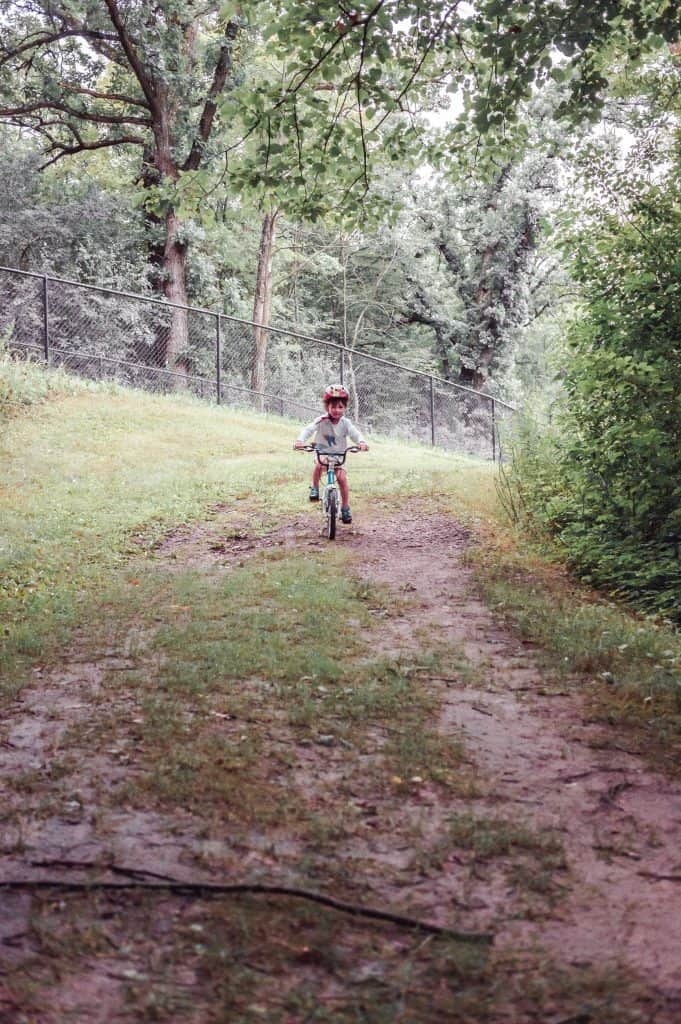Woom bikes | Toddler on a woom 2 racing down a forest trail.
