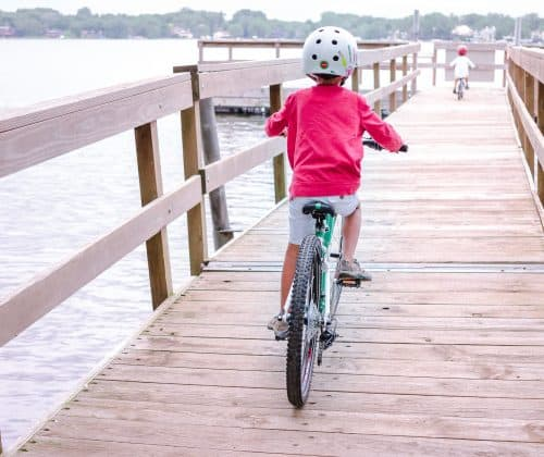 Woom 5 - Kids biking on a pier over a lake.