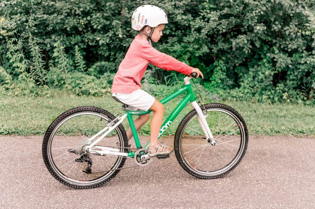 Woom 5 Bike Review | My child riding the new woom five green bike in a helmet on a trail.