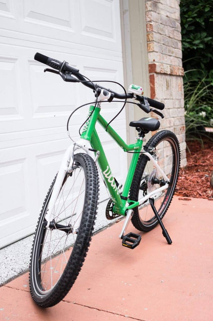Woom 5 Bike Review | Green woom 5 bike on a kickstand. Tires are thicker.