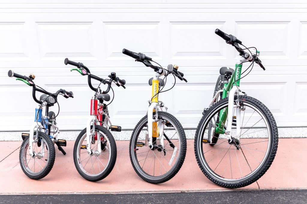 Woom 5 Bike Review | A collection of woom 2-5 standing in the driveway in 4 colors.