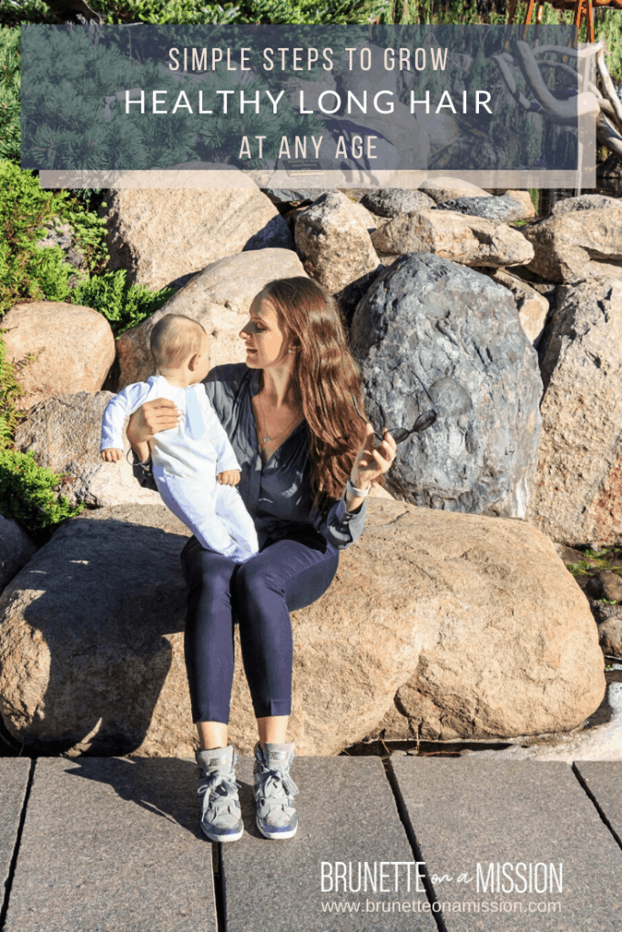 How to Grow Long Healthy Hair - I'm sitting with baby Ilan on the rocks near a waterfall with my long hair shining in the sun.