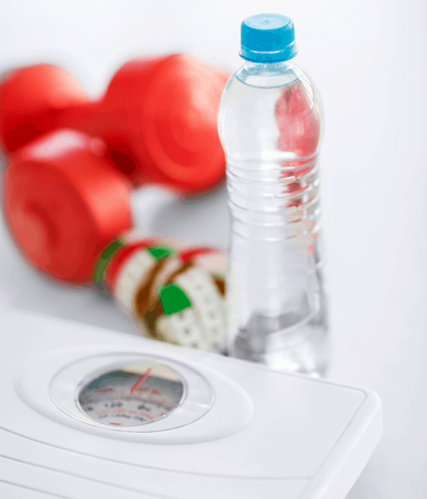 Simple Intermittent Fasting Workout Plan - A set of red dumbbells with a water bottle and a scale on the floor.