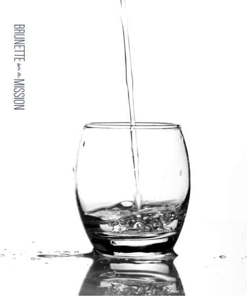 What is the Best Water to Drink -Image showing a clear short glass being poured with water on a white background.
