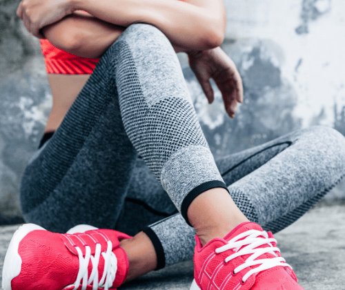 7 Fitness Goals Women (and Men) Should Make | Fit woman sitting on a concrete floor in workout clothes.