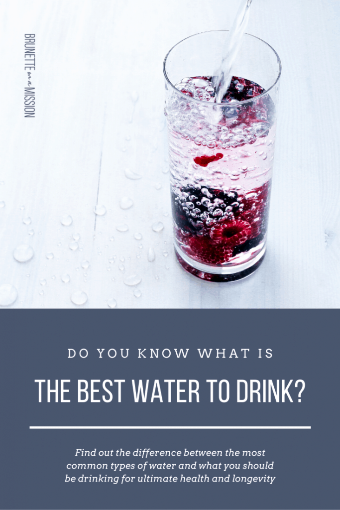 What is the Best Water to Drink for Health? - Clear tall glass standing on a white tabletop and being filled with water. There are black and red berries on the bottom.
