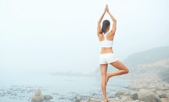 Beautiful lean woman practicing yoga on a foggy morning on the beach - Autophagy and Fasting - the Secret to Anti-Aging | Brunette on a Mission