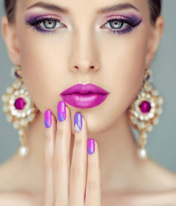Closeup shot of a beautiful young woman with a polished bright pink and purple manicure and makeup| Artificial Nails - All the Different Types of Fake Nails