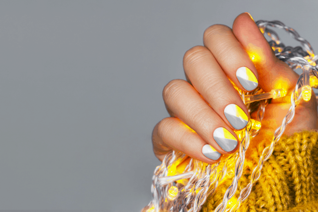 Shot of a hand with a beautiful abstract manicure holding a lit strand of warm white christmas lights against a gray background | What are Fiberglass Nails and How to Apply Them? | Brunette on a Mission