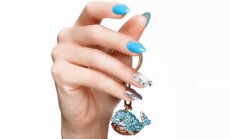 Shot of a hand with a beautiful blue and white manicure holding a small blue crystal keychain against a white background | What are Fiberglass Nails and How to Apply Them? | Brunette on a Mission