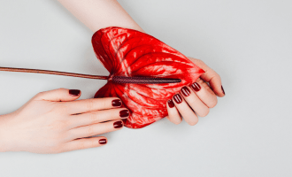 Two hands with red manicure holding a red calla lily flower.| The Best Guide to Nail Wraps, Nail Stickers & Nail Decals| Brunette on a Mission
