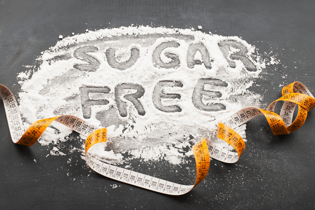 Sugar Free spelled in an artificial sweetener powder with a finger on a dark surface. | Don't Break Your Fast! Your Complete Guide to Sweeteners.